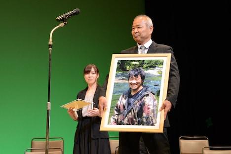 舟山弘一の写真とともに登壇する辻井啓司(手前)と、代理登壇した舟山の夫人(奥)。