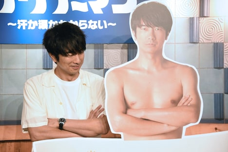 自分のパネルとの2ショット撮影に戸惑う眞島秀和(左)。