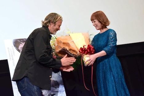 佐藤仁美(右)から花束を受け取るマッツ・ミケルセン(左)。