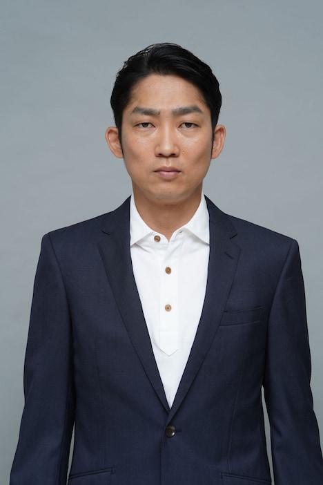 石田明演じる尾崎賢治。