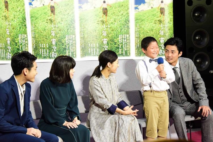 藤原颯音(中央右)を見守る共演者たちと、隣からささやく毎熊克哉(右)。