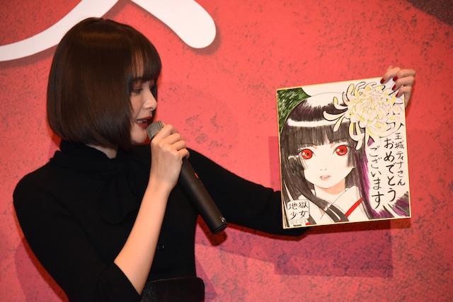 テレビアニメ「地獄少女」のキャラクターデザインを担当した岡真里子描き下ろしのイラスト色紙をプレゼントされた玉城ティナ。