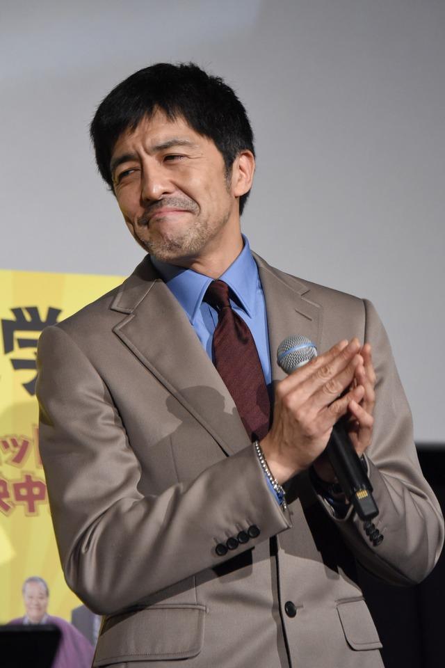 感慨深げに西田敏行の歌を聴く谷中敦。
