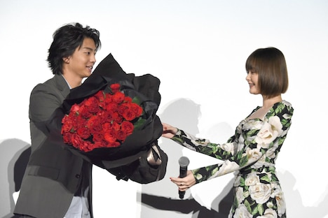 バラの花束を玉城ティナ(右)に手渡す伊藤健太郎(左)。