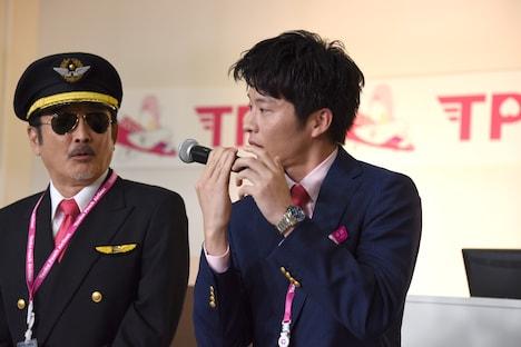 機内アナウンス用マイクの持ち方を再現する田中圭(右)。