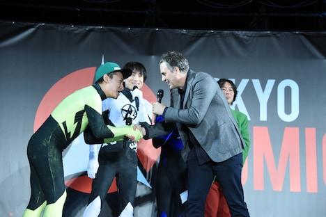 佐藤ピリオド(手前左)と握手するマーク・ラファロ(手前右)。