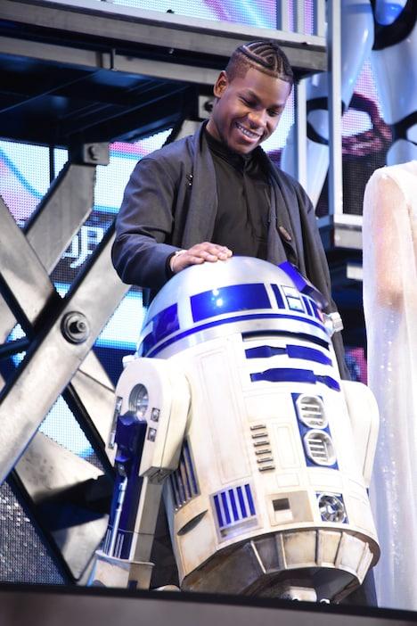 R2-D2に手を添えるジョン・ボイエガ。