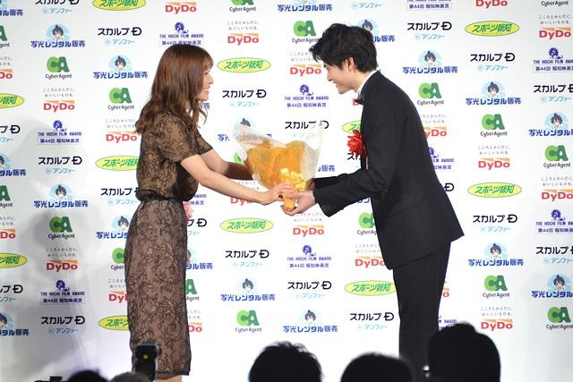 鈴鹿央士(右)に花束を渡す松岡茉優(左)。
