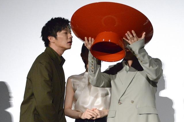 残りの酒の量を確認する田中圭(左)。