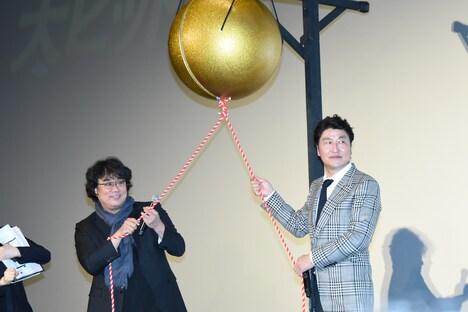 くす玉を割ろうとするポン・ジュノ(左)とソン・ガンホ(右)。