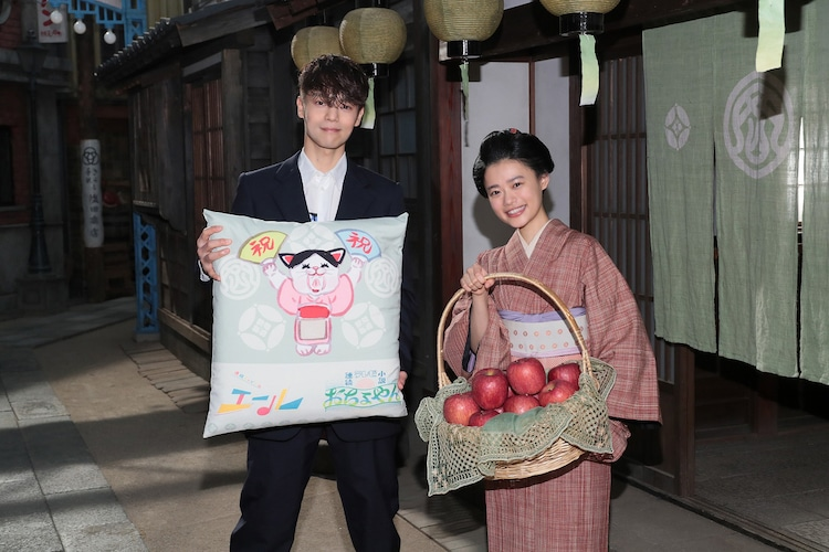 特製座布団を持つ窪田正孝(左)と、福島産の木成り完熟りんごを受け取った杉咲花(右)。