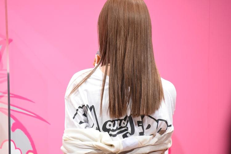Tシャツのバックプリントをアピールする生見愛瑠。