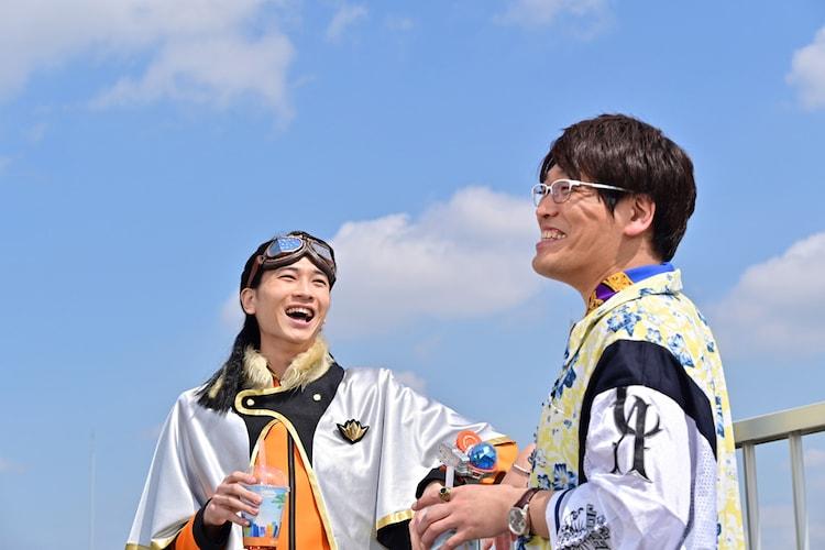 「博士じゃないよ、博多だよ!しかも南だよ!」ミュージックビデオより、庄司浩平演じるクリスタリア宝路(左)と古坂大魔王演じる博多南無鈴(右)。