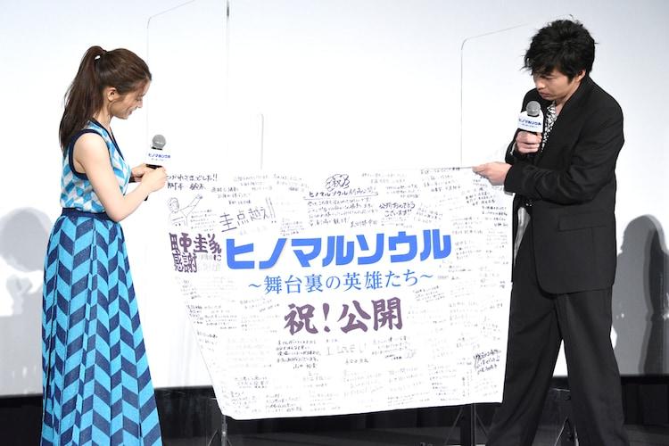 フラッグを広げる田中圭(右)と土屋太鳳(左)。