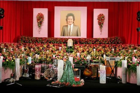 式場内は紅白の横断幕をバックに、多数の花やCandle JUNEの手による100本近いキャンドルが飾られた。
