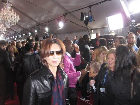 革ジャンにスカーフをあわせたシンプルな着こなしで、報道カメラに向けおだやかな視線を送るYOSHIKI。