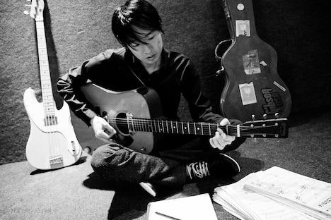 アコースティックギターを弾く小沢健二。写真は2010年4月に撮影された最新のカット。