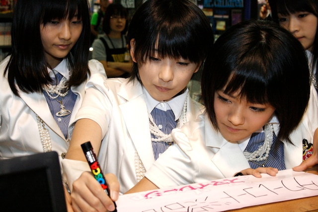最後にタワーレコード渋谷店へのメッセージを書く福田花音(写真左から2番目)と、それを見つめるメンバー。