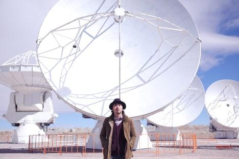「ALMA」のビデオクリップ撮影のためにチリを訪れた大木伸夫。後ろはパラボラアンテナ。