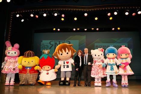 写真左よりマイメロディ、ポムポムプリン、いちごの王さま、タボくん、西川、佐藤社長、ハローキティ、キキ&ララ。