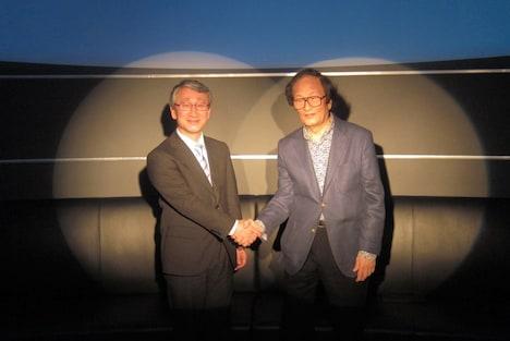 写真はアルバム「惑星 ultimate edition」完成発表会の様子。握手を交わす川口淳一郎(写真左)と冨田勲(右)。