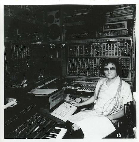 1970年代、壁一面を覆うシンセサイザーに囲まれた冨田勲。