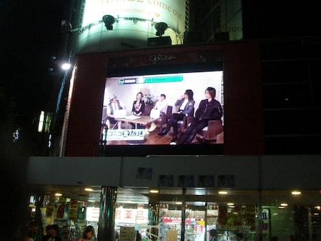 写真は渋谷の街頭ビジョンで行われたサプライズ生中継の模様。