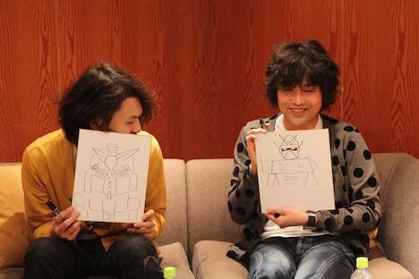お絵描きコーナーの1問目「ガンダム」を互いに披露する山中さわおと菅原卓郎。