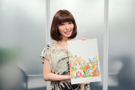 配信シングル「キミニトドケ」のジャケット原画を手にした相沢舞。このイラストはマンガ家・あらゐけいいちの描き下ろしによるもの。