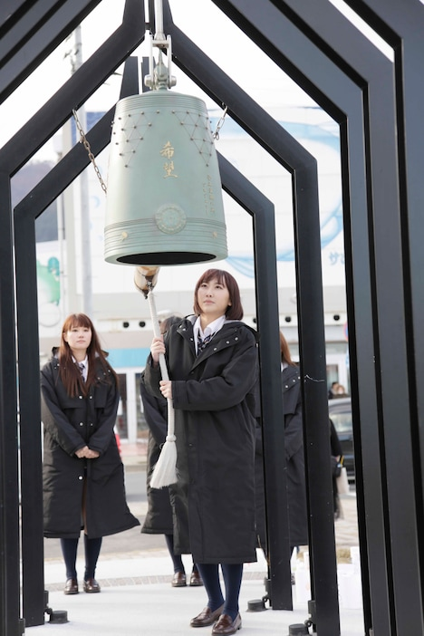 釜石駅前に設置された「復興の鐘」を鳴らす仁藤萌乃。(C)AKS