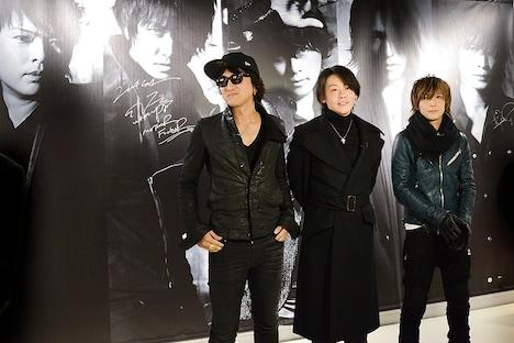 自分たちの特大写真の前に立つJ、RYUICHI、INORAN。