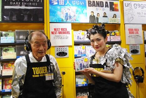 宇宙人「じじい」を試聴する菅登未男と、シングルを手に持つしのさきあさこ。