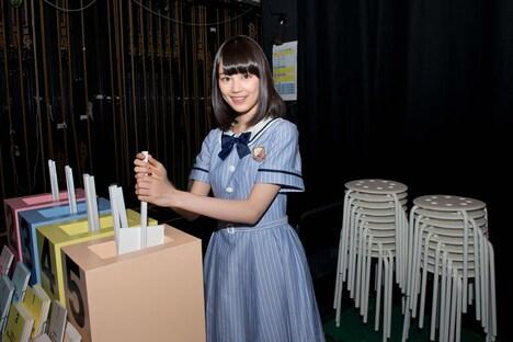ステージ袖に準備されている、1幕のコントのくじびき箱を紹介する生田絵梨花。
