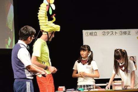 流暢な英語でジョセフ・テイムと会話する日高麻鈴と、その横で黙々と作業を続ける吉田爽葉香。