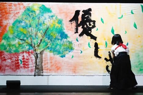 美術部のイラストに「優しさ」の文字を添える欅坂46書道部・尾関梨香。(写真提供:Sony Music Records)
