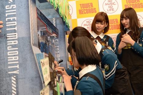 陳列用ポップにサインを書き入れる欅坂46メンバー。