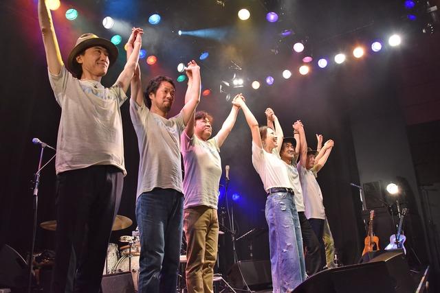バンドメンバーと手をつないで挨拶する加藤いづみ。