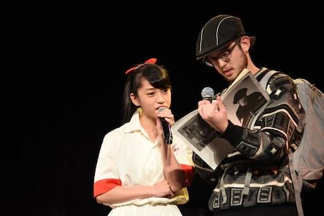 道に迷った外国人(サンディー・カイ / 右)と、古いガイドブックを前に困り顔のmei(左)。