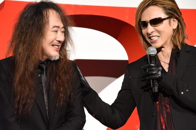 PATA(左)の肩を叩くYOSHIKI(右)。
