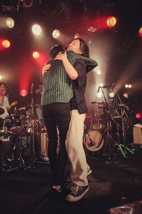 抱き合う米田貴紀(Vo, G / 夜の本気ダンス)と須藤寿(Vo, G / 髭)。(Photo by Wataru Umeda)
