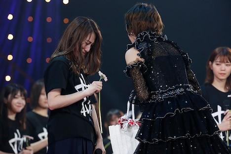 若月佑美(右)に花を渡され涙する桜井玲香(左)。(写真提供:ソニー・ミュージックレコーズ)