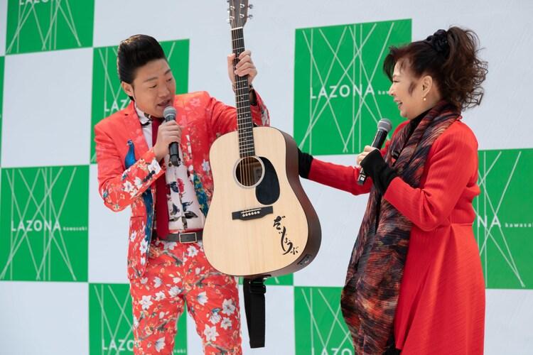 八代亜紀からアコースティックギターを受け取るみやぞん。(Photo by Tomokazu Tazawa)