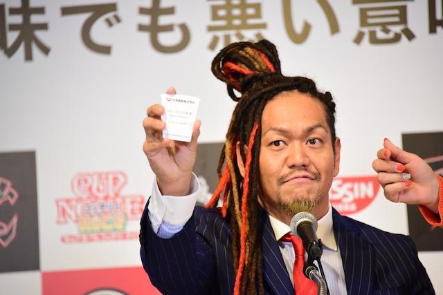 「カップヌードル コッテリーナイス」広告代理人の名刺をアピールするマキシマムザ亮君。