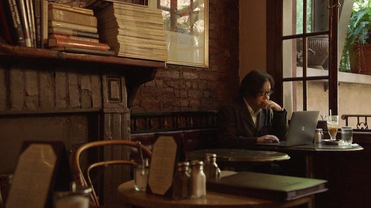 「川の流れのように」を作詞した場所・ニューヨークのイーストリバー近くのカフェで新曲「あれから」を作詞する秋元康。(写真提供:NHK)