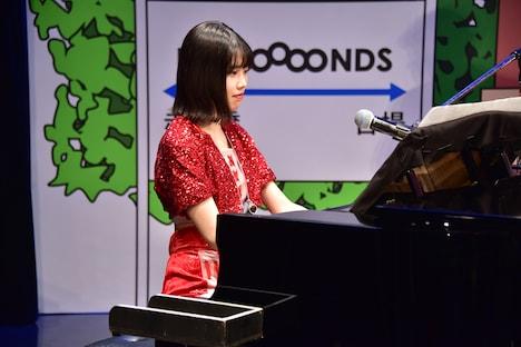 ピアノで「眼鏡の男の子」のメロディを弾く小林萌花。