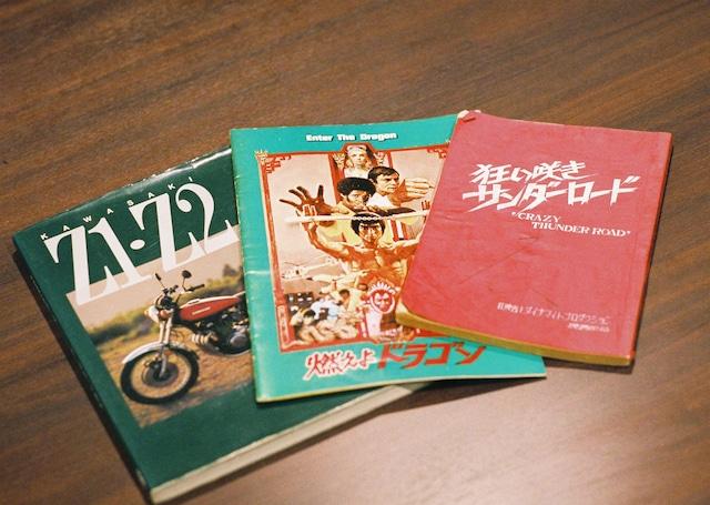 左からカワサキZ1・Z2の解説本、ブルース・リー主演の映画「燃えよドラゴン」のパンフレット、映画「狂い咲きサンダーロード」の脚本(セイジ私物)。