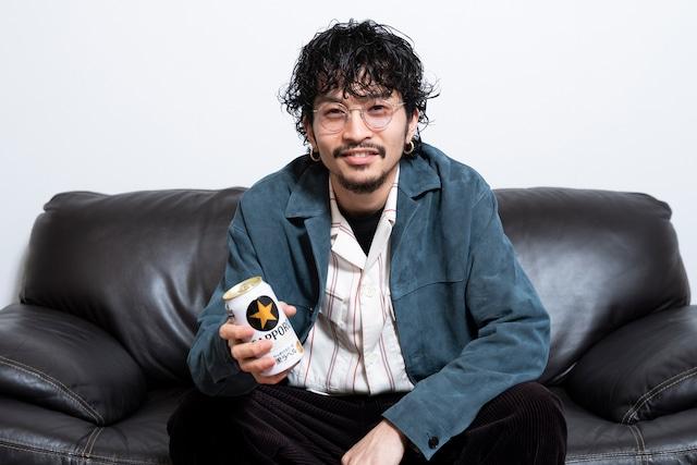 「サッポロ生ビール黒ラベル」を持って微笑む常田大希。