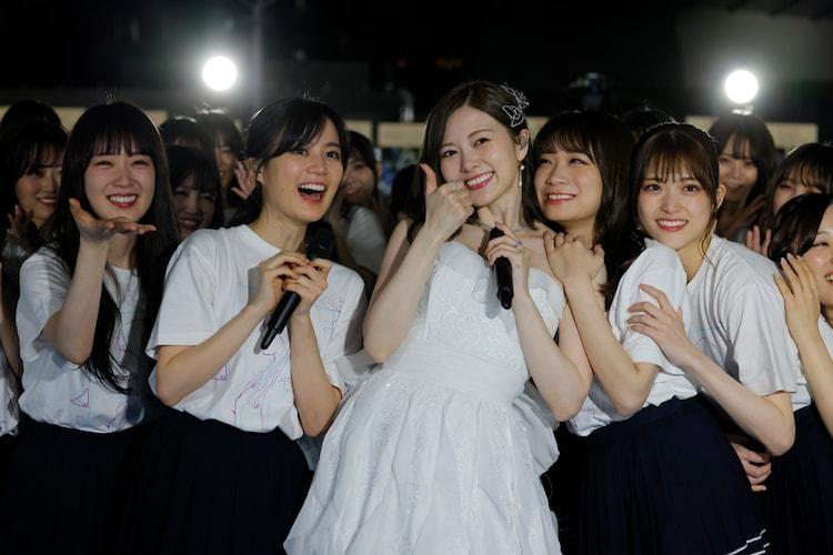 メンバーとカメラに向かって笑顔を送る白石麻衣。(写真提供:ソニー・ミュージックレーベルズ)