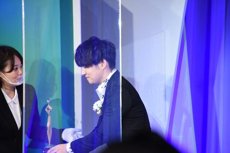 トロフィーを受け取る藤原聡(Vo, Piano)。