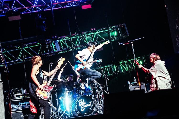 曲のクライマックスでドラムセットからジャンプするミキの亜生(写真中央)。(撮影:浜野カズシ)
